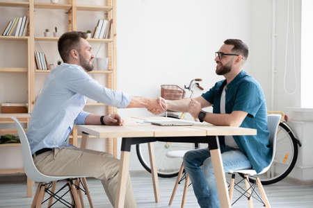 Smiling businessmen shake hands close deal after successful interview in office. Happy employer handshake candidate or business partner make agreement or get acquainted at meeting. Employment concept. Stock fotó