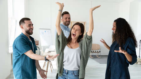 Banner panoramic view of overjoyed multiracial young employees have fun celebrate win or victory in office. Happy diverse multiethnic colleagues feel excited dance triumph together at workplace.