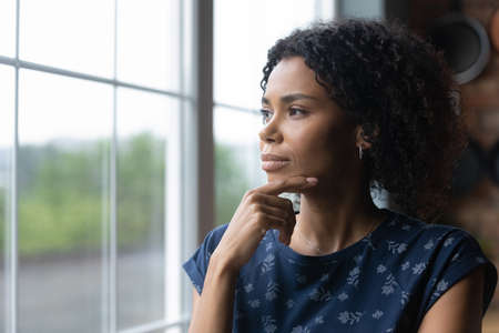 Thoughtful millennial african american woman standing near window, recollecting memories or feeling lonely at home. Pensive young biracial lady contemplating, lost in thoughts, vision concept.