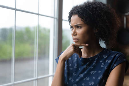 Unhappy young african ethnicity woman looking out of window, thinking of life problems, copy space. Frustrated lost in thoughts millennial mixed race lady feeling doubtful making difficult decision.