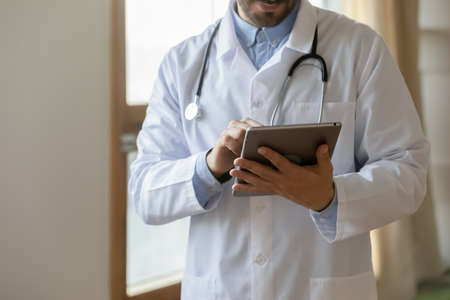 Crop close up of male doctor in white medical uniform consult client online on tablet gadget in hospital. Man GP use fil medical anamnesis or card on pad in modern private clinic. Healthcare concept.