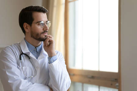 Pensive young male doctor in white medical uniform glasses look in window distance thinking. Thoughtful Caucasian man GP lost in thoughts, make decision in hospital. Medicine, healthcare concept
