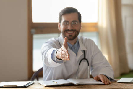 Close up blurred of smiling male doctor stretch hand greeting with patient or client at consultation in hospital. Man GP sit at desk get acquainted meet customer in private clinic. Medicine concept.