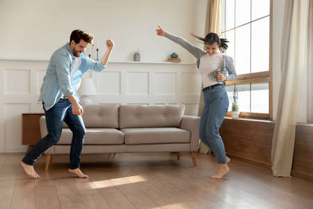 Happy millennial Caucasian couple renters dance celebrate relocation to new own apartment together. Overjoyed young husband and wife man and woman have fun enjoy weekend at home. Moving concept.