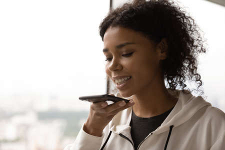 Close up of young African American woman record audio message on cellphone device. Millennial biracial female activate digital virtual voice assistant on modern smartphone. Technology concept.