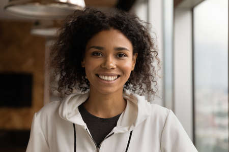 Profile picture of smiling young African American woman talk on video call in office. Headshot portrait of happy millennial biracial female employee show confidence and success. Leadership concept.
