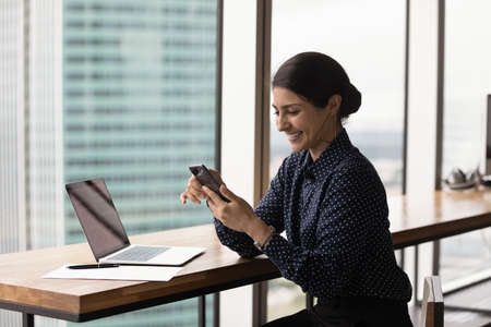 Smiling millennial Indian woman sit at desk in office use computer text or message on smartphone gadget. Happy young ethnic female browse internet communicate on cellphone. Technology concept.