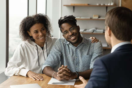 Smiling biracial man and woman talk with male real estate agent at office meeting. Happy African American young couple consult with realtor or broker, buy first shared house together. Rental concept.
