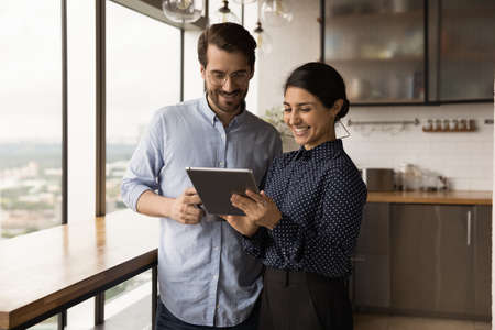 Smiling multiracial young colleagues look at tablet screen discuss financial business online project on gadget. Happy diverse multiethnic coworkers cooperate use pad device at work break in office.
