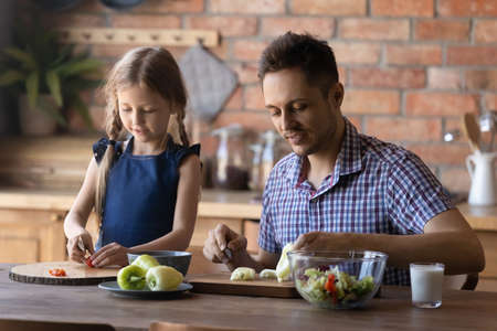 Close up smiling caring father and little daughter chopping vegetables, cooking salad together, sitting at wooden table in kitchen at home, preparing meal, dad and child enjoying leisure time