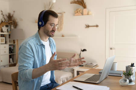 Confident man wearing glasses and headphones making video call, using laptop, sitting at work desk, home office, engaged in online negotiations, internet meeting, mentor coach leading webinar