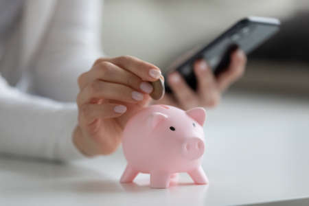 Close up woman holding smartphone, putting coin in pink piggy bank, young female browsing online banking service, planning budget, investment strategy, saving money, checking finances