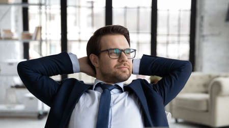 Close up dreamy businessman wearing suit and glasses leaning back in comfortable office chair, dreaming, successful entrepreneur stretching hands, enjoying break, visualizing future, stress relief