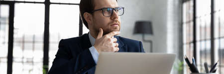 Close up thoughtful motivated businessman wearing glasses looking to aside in office horizontal banner, touching chin, sitting with laptop, pensive entrepreneur planning, pondering business strategy
