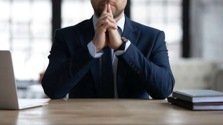 Close up confident thoughtful businessman wearing suit sitting at work desk, pensive employee executive touching chin, solving problems, making difficult decision, pondering project strategy