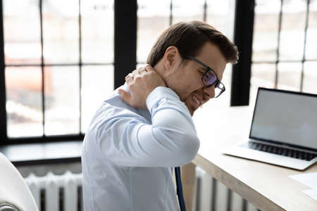 Close up depressed stressed young employee suffering from pain in neck, touching massaging stiff muscles, unhappy businessman worker feeling unwell after long hours sedentary work in office