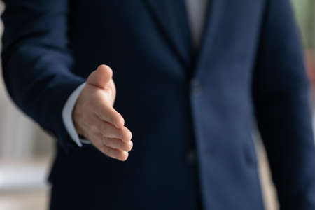 Close up businessman wearing suit extending hand for handshake to business partner or customer at meeting, hr manager greeting candidate at job interview, first impression or acquaintance Foto de archivo