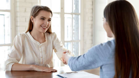 Wide banner view of smiling businesswomen handshake get acquainted greeting at meeting in office. Happy female employer shake hand close deal with candidate or applicant after successful interview.