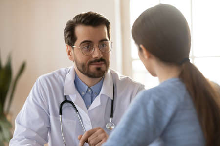 Attentive young Caucasian male doctor talk listen to female patient complaints at consultation in hospital. Man GP or physician speak consult woman client, discuss illness disease. Healthcare concept.
