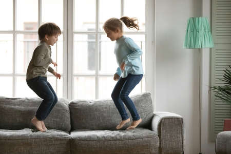 Energetic little kids siblings jumping barefoot on couch, enjoying spending free weekend leisure time together at home. Happy small preschool brother and sister involved in funny domestic activity.