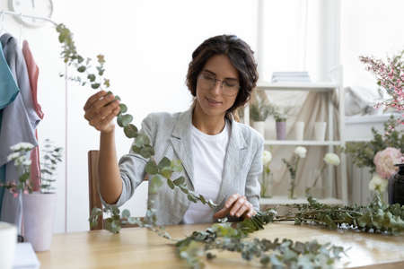 Got an idea. Thoughtful young lady floral decor specialist sitting at work desk looking at fresh green branch imagining bouquet. Inspired woman skilled in floristics visualizing beautiful composition