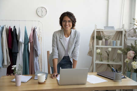 When hobby becomes business. Portrait of successful young woman designer dressmaker florist looking at camera with happy smile. Female owner of workshop studio atelier posing by desk enjoying work Reklamní fotografie