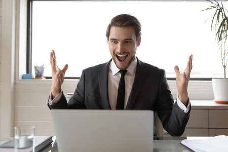Overjoyed young Caucasian businessman feel euphoric read good amazing news online on laptop. Excited male CEO sit at desk in office triumph get business win on computer. Luck, success concept.