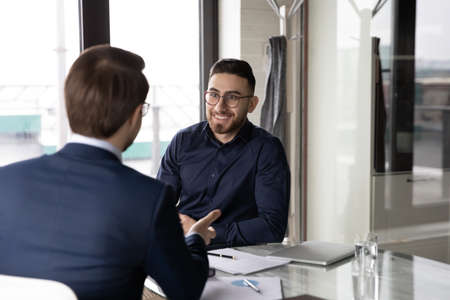 Smiling young Arabic businessman talk consult with male colleague coworker at meeting in office. Happy motivated international multiracial businesspeople brainstorm at briefing. Partnership concept.