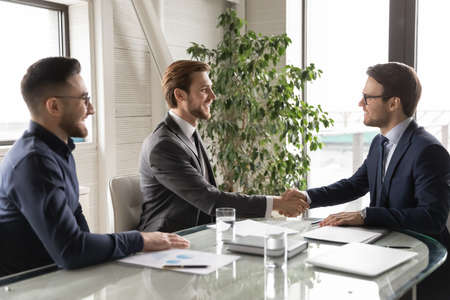 Happy multiracial young businessmen shake hands closing successful business deal at office meeting. Smiling diverse international businesspeople partners handshake get acquainted greeting at briefing. Stockfoto