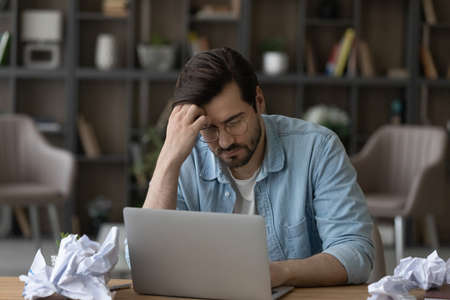 Unhappy millennial Caucasian man sit at desk at home office with draft paperwork meet deadline. Upset exhausted young male employee work on laptop overwhelmed with job. Overwork concept.