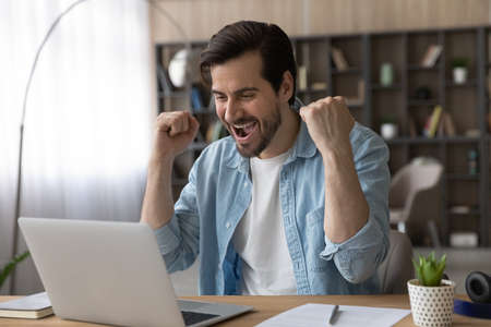 Excited young Caucasian man look at laptop screen feel euphoric celebrate online lottery win. Overjoyed millennial male triumph reading good news on computer, get promotion email letter. Luck concept.