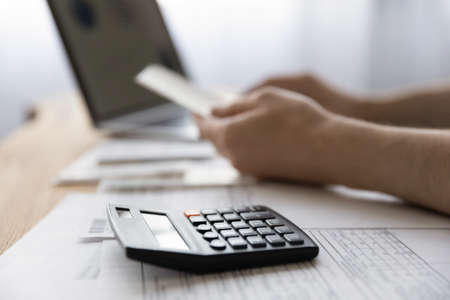 Crop close up of man sit at home desk work on laptop calculate household expenses expenditures on calculator. Male busy with paperwork document, manage house family finances or budget online.