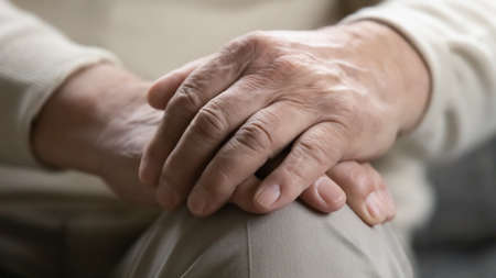 Time teaches us patience. Close up view of older generation male palms joined on his lap. Problems of retired people. Health failing with age. Patronage and psychological support for elderly persons