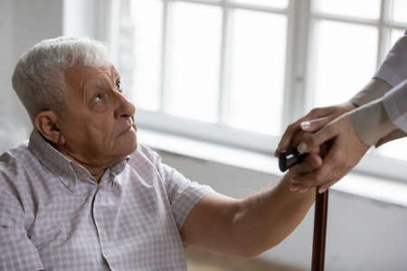 Disabled elderly male receive help compassion aid from home care nurse retreat center staff. Mature man with walking problems get professional support of attentive doctor therapist on rehabilitation