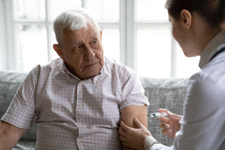 Good hand. Sick elderly male receiving medical procedures at home. Qualified professional nurse giving intramuscular shot injection of medicinal preparation drug in arm of adult elderly man patient