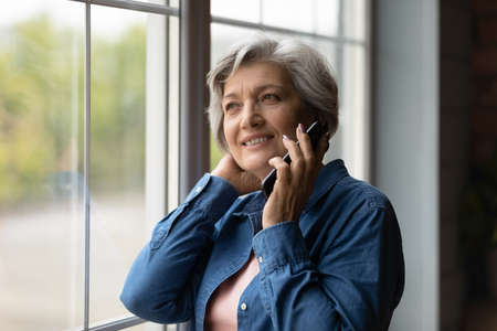 Happy middle aged 50s woman standing near window, enjoying pleasant mobile phone conversation with friends. Smiling dreamy older mature lady communicating distantly by smartphone call indoors.