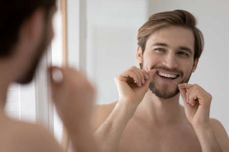 Happy millennial european appearance shirtless man cleaning teeth with dental floss, looking in mirror. Smiling young guy enjoying morning or evening oral daily routine after shower in bathroom.