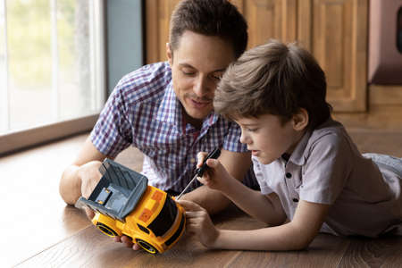 Little handyman. Focused son kid lying on warm wood floor fix toy car with help of young daddy. Junior boy listen to father advices learn to use screwdriver tool imitating dad activity at repair work Stock Photo