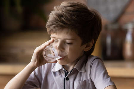 What a pleasure. Happy junior school age boy drinking pure fresh clear potable water from glass refreshing himself at hot day. Delighted small kid swallow cool aqua in little sips enjoy natural taste