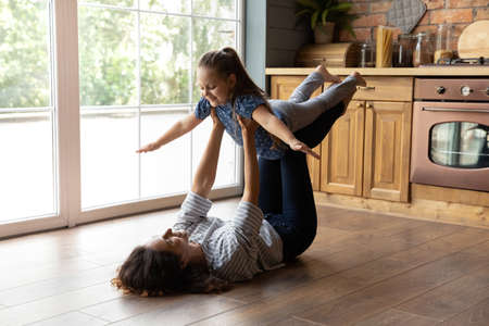 Cute gymnastics. Happy smiling young mom supporting little daughter in air doing flying plane exercise. Grown elder sister playing active game with younger girl lying on heated floor at home kitchen