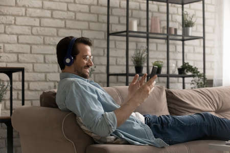 Alone on weekend. Happy young male enjoying rest on cozy couch playing mobile game in wireless headphones. Content man listen music from smartphone playlist or choose audio book at online library Archivio Fotografico