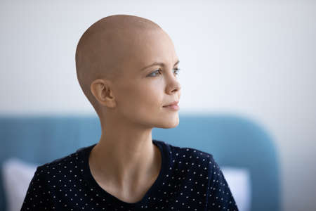 Ready to fight for life. Thoughtful sick young woman with light smile look aside planning struggle with cancer. Pensive hairless female oncology patient dream of happy future after defeating disease