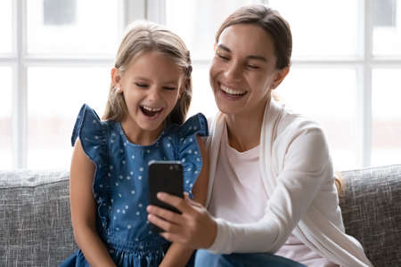 Close up happy mother with little daughter using phone together, looking at screen, watching cartoons or making video call, sitting on couch at home, young mum and child having fun with smartphone
