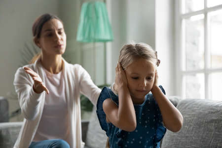 Close up upset little girl covering ears, ignoring angry yelling mother, sitting on couch back to mum scolding daughter, child and parent conflict, two generations misunderstanding, bad relationship Standard-Bild