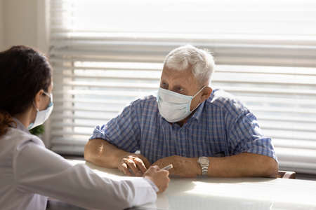 Mature 80s male patient in medical facemask have consultation with female doctor in hospital. Woman GP or therapist talk consult with senior man client in facial mask. Elderly healthcare concept.