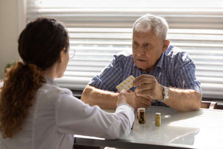 Woman GP or therapist give recommend pills or drugs to unhealthy mature male patient in clinic. Caring female doctor prescribe medicines to sick senior man client. Elderly healthcare concept.