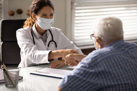 Smiling young female doctor in facial mask shake hand get acquainted with mature male patient in clinic. Happy woman GP in medical facemask handshake elderly client in hospital. Corona concept.