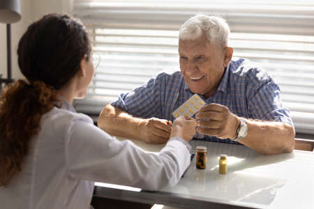 Back view of female doctor give pills medication to smiling mature male patient in private hospital. Woman GP or nurse recommend treatment, offer drugs medicines to happy elderly man client in clinic.