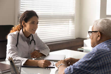 Attentive young Caucasian female doctor talk consult mature male patient in clinic. Caring woman GP or nurse speak have consultation with elderly man client in private hospital. Geriatrics concept.