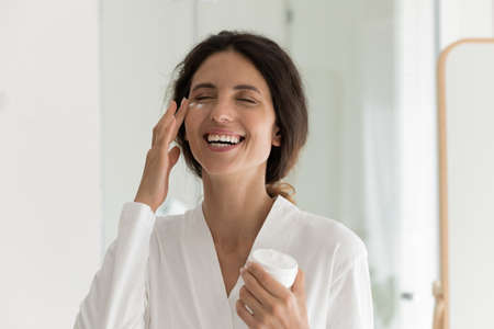 Overjoyed millennial woman apply moisturizing face cream for healthy glowing skin. Smiling young Caucasian female do facial beauty procedures or treatment, use nourishing balm. Skincare concept.